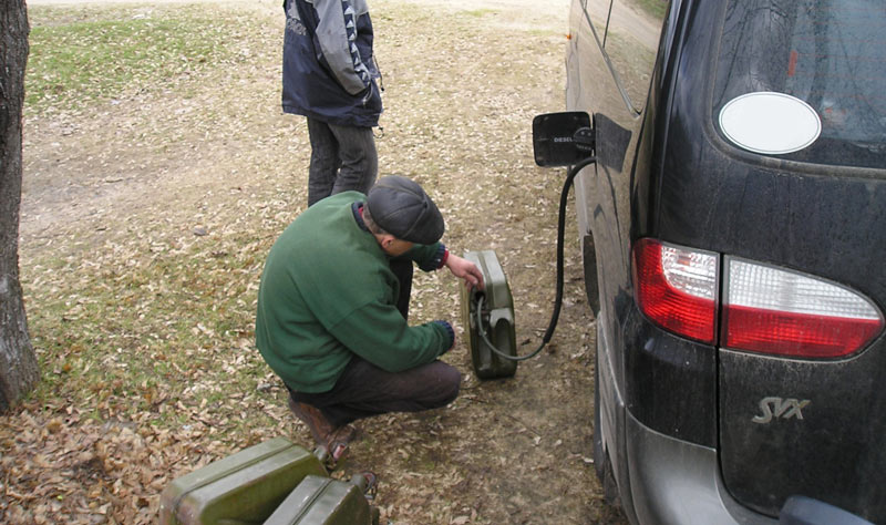 Слив бензина из бака машины.
